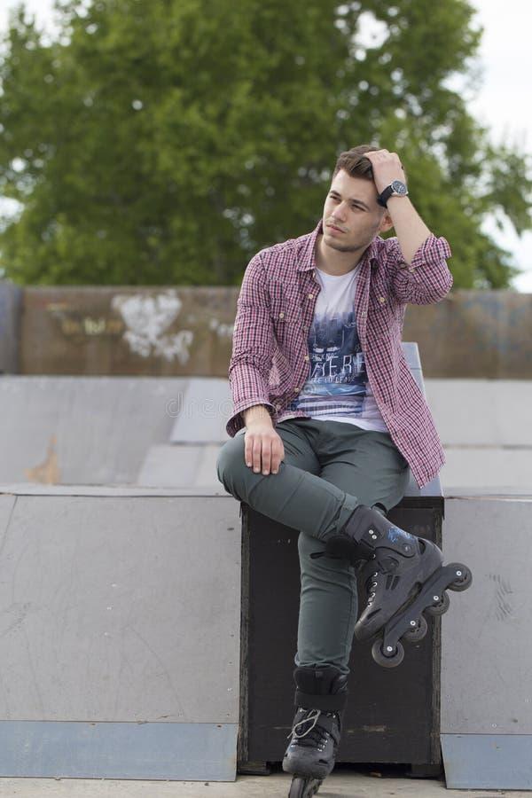 El hombre joven hermoso con los pcteres de ruedas se sienta y goza fotografía de archivo