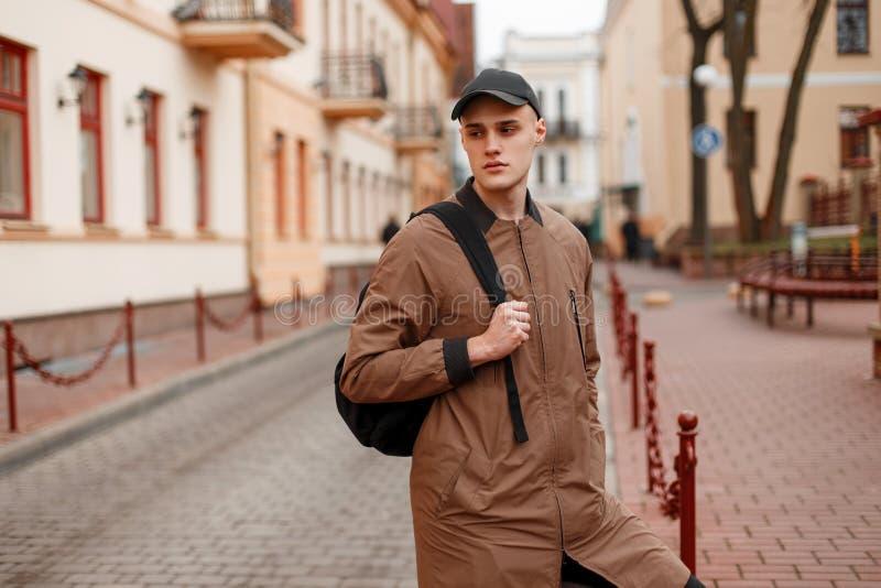 El hombre joven hermoso de moda americano en una chaqueta larga beige elegante en un casquillo elegante con una mochila negra cam fotografía de archivo libre de regalías