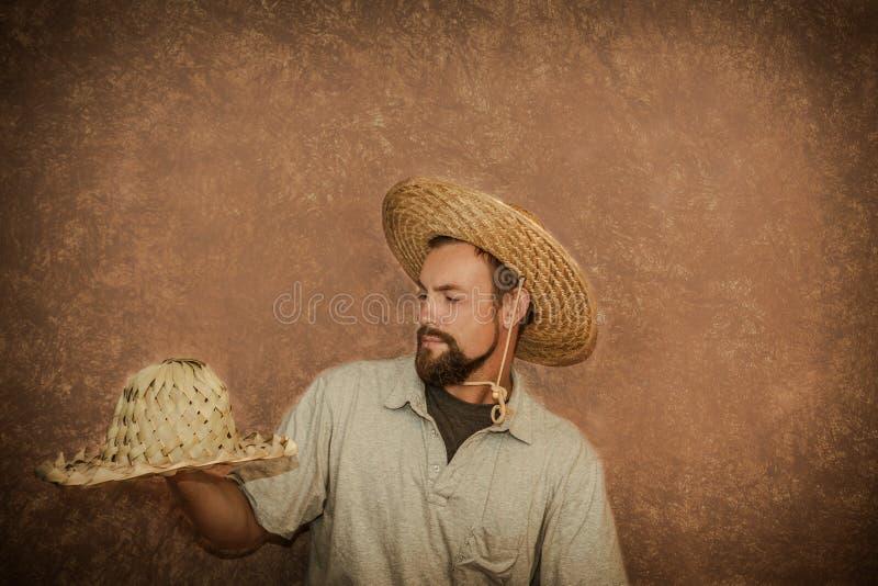 El hombre joven hermoso demuestra los sombreros de paja de moda fotos de archivo libres de regalías