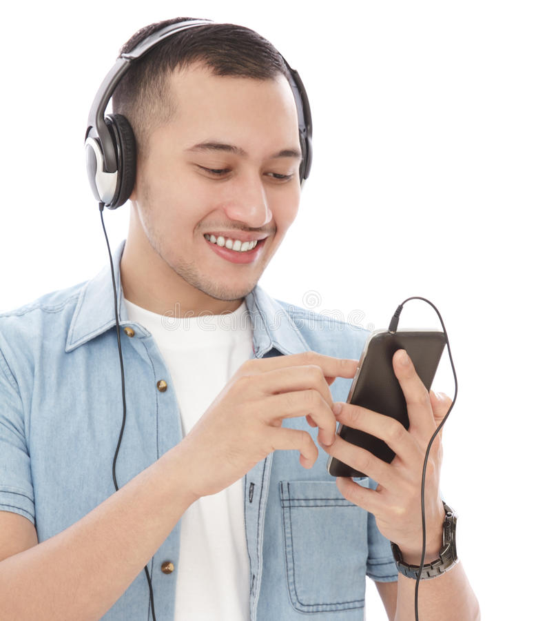 El hombre joven hermoso disfruta de música que escucha en el móvil con hea fotografía de archivo