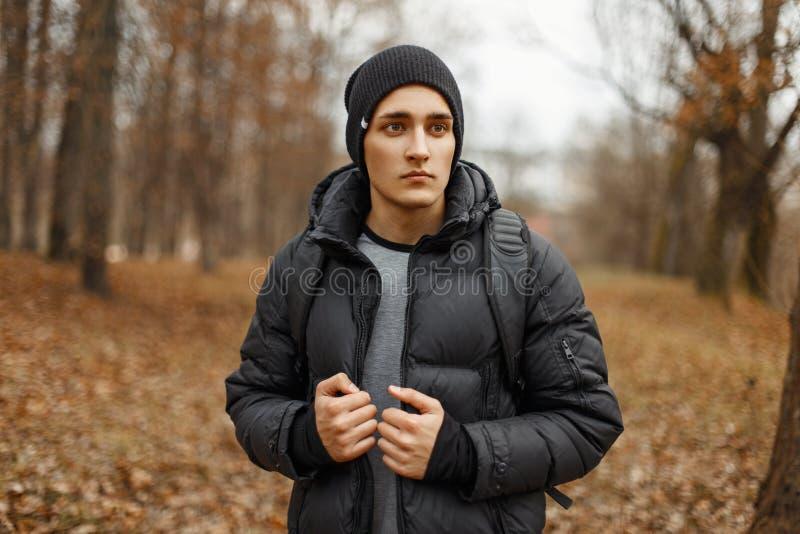 El hombre joven hermoso en invierno viste con una mochila fotografía de archivo libre de regalías