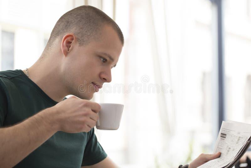 El hombre joven hermoso se relaja mientras que bebe que primera taza de coff imagen de archivo