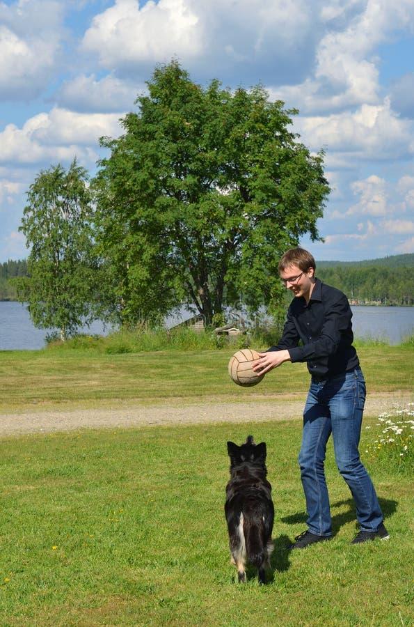 El hombre joven juega con el perro con la bola en prado Laponia finlandesa fotos de archivo