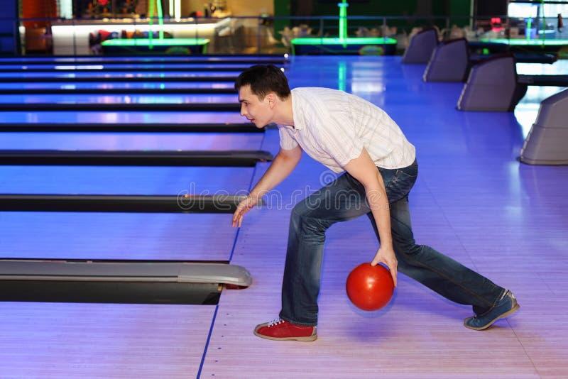El hombre joven lanza la bola en el bowling imágenes de archivo libres de regalías