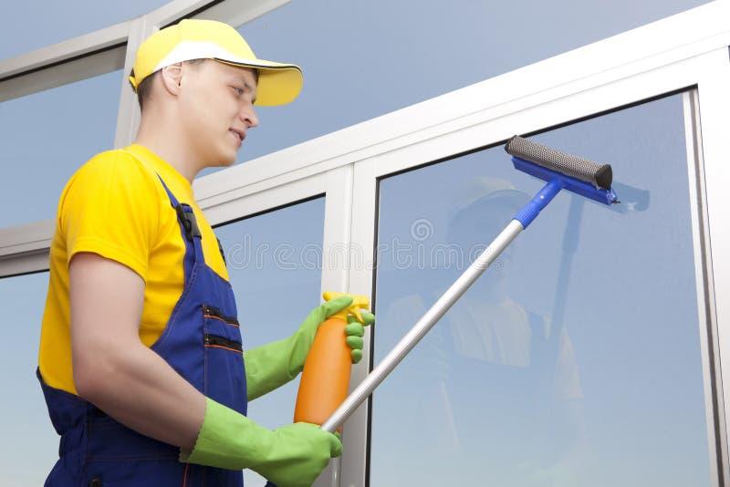 El hombre joven lava la ventana fotografía de archivo