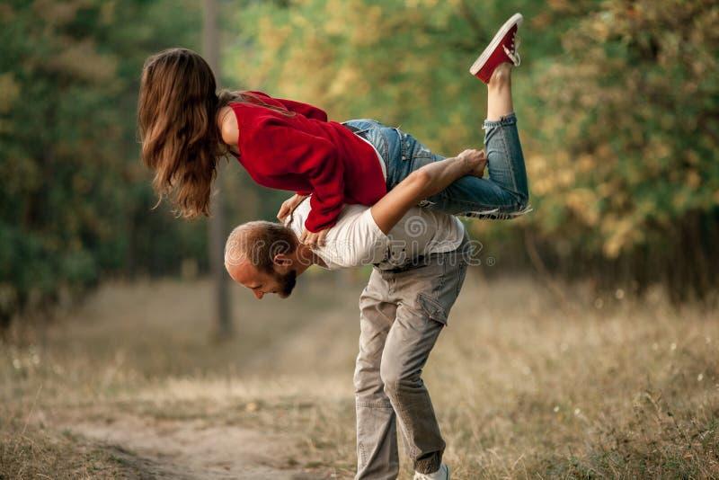 El hombre joven levantó para arriba a la muchacha en el suyo parte posterior y la lleva fotografía de archivo