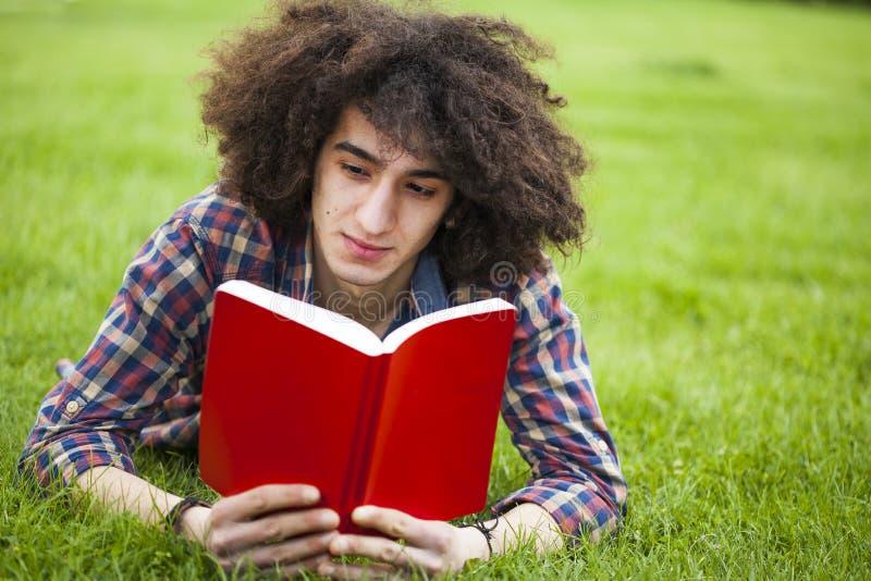 El hombre joven leyó el libro en hierba fotos de archivo