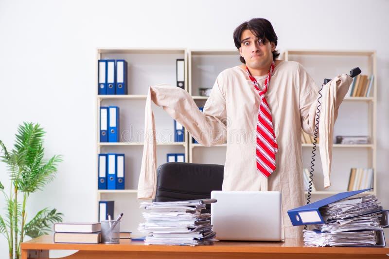 El hombre joven loco en camisa de fuerza en la oficina fotos de archivo