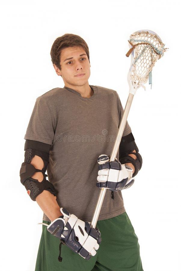El hombre joven moreno en lacrosse rellena sostener el palillo fotografía de archivo