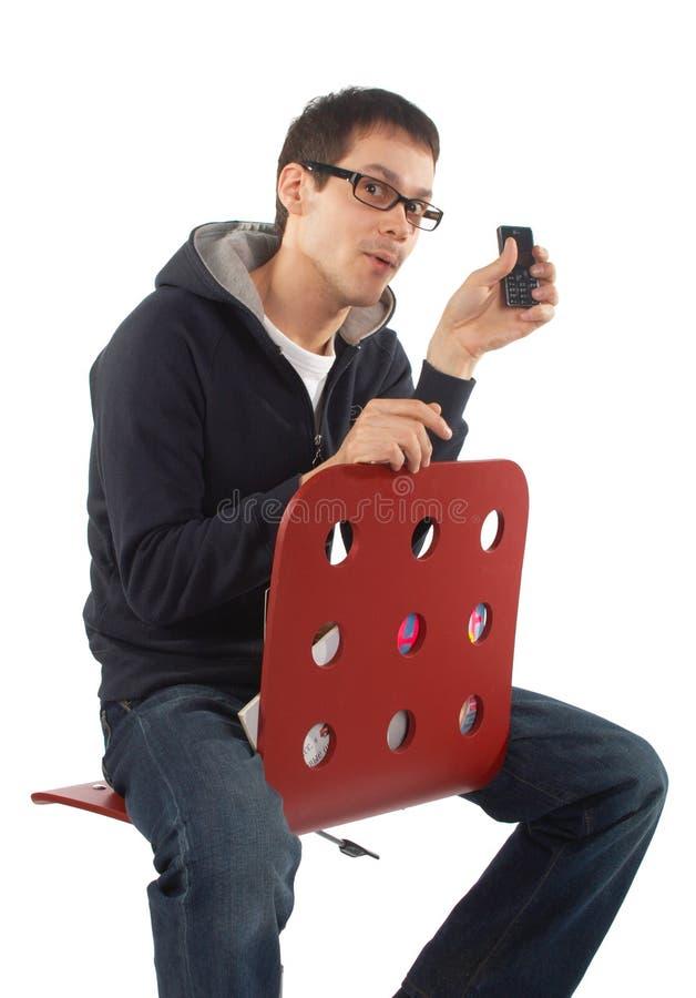 El hombre joven muestra el teléfono celular que se sienta en taburete imágenes de archivo libres de regalías