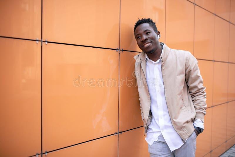 El hombre joven negro hermoso en una chaqueta y una camisa blanca está escuchando la música con los auriculares fotos de archivo libres de regalías