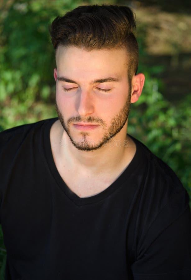 El hombre joven pacífico con los ojos se cerró, relajándose al aire libre en naturaleza foto de archivo