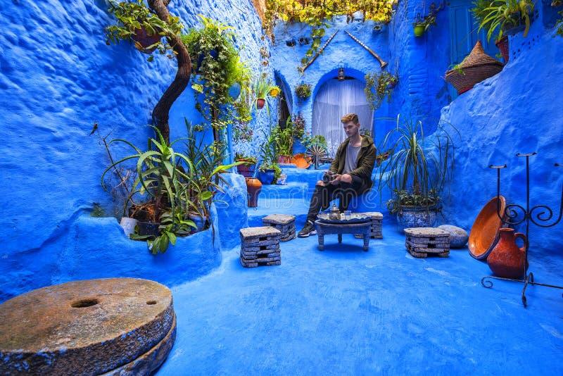 El hombre joven pensativo de aspecto europeo se sienta en un patio acogedor hermoso fantástico en el Medina foto de archivo