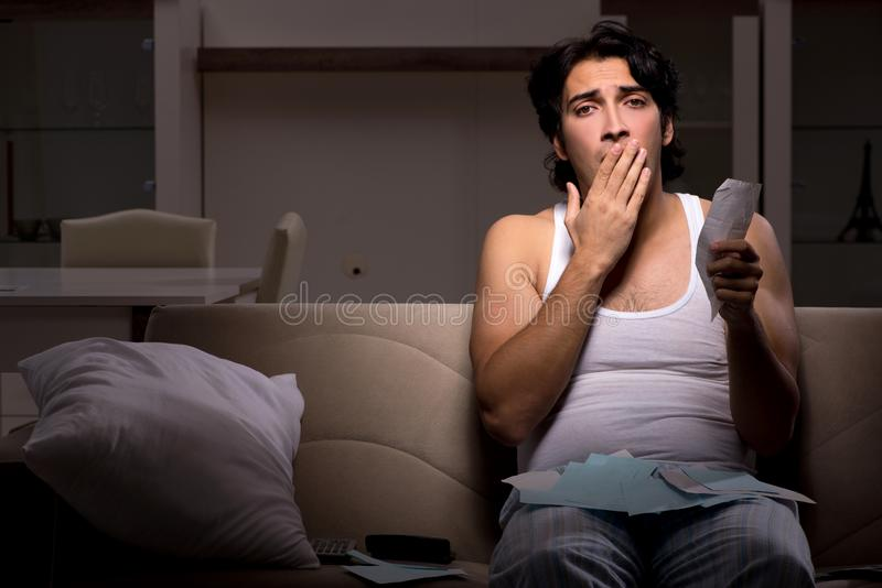 El hombre joven que calcula noche de los expences en casa fotografía de archivo libre de regalías