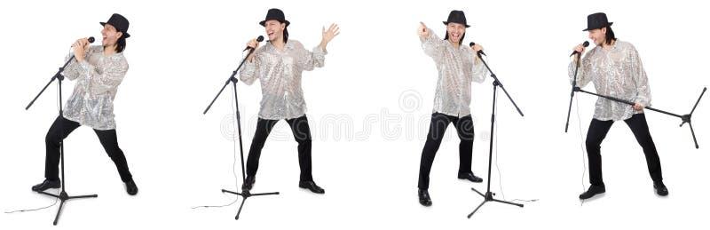 El hombre joven que canta con el micrófono aislado en blanco foto de archivo