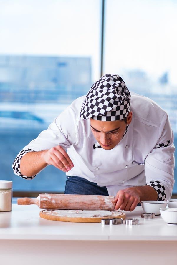 El hombre joven que cocina las galletas en cocina imagen de archivo