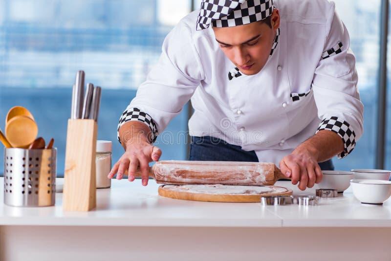 El hombre joven que cocina las galletas en cocina imagenes de archivo