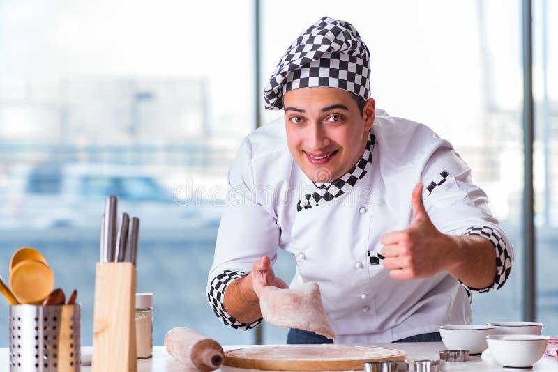 El hombre joven que cocina las galletas en cocina imagen de archivo libre de regalías