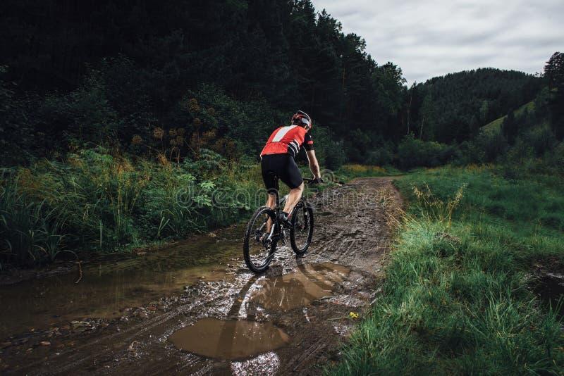 El hombre joven que completa un ciclo en el paseo de la bici de montaña a campo través fotos de archivo libres de regalías