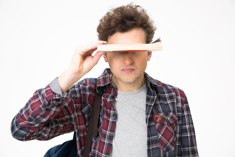 El hombre joven que cubre el suyo observa con el libro imagen de archivo libre de regalías
