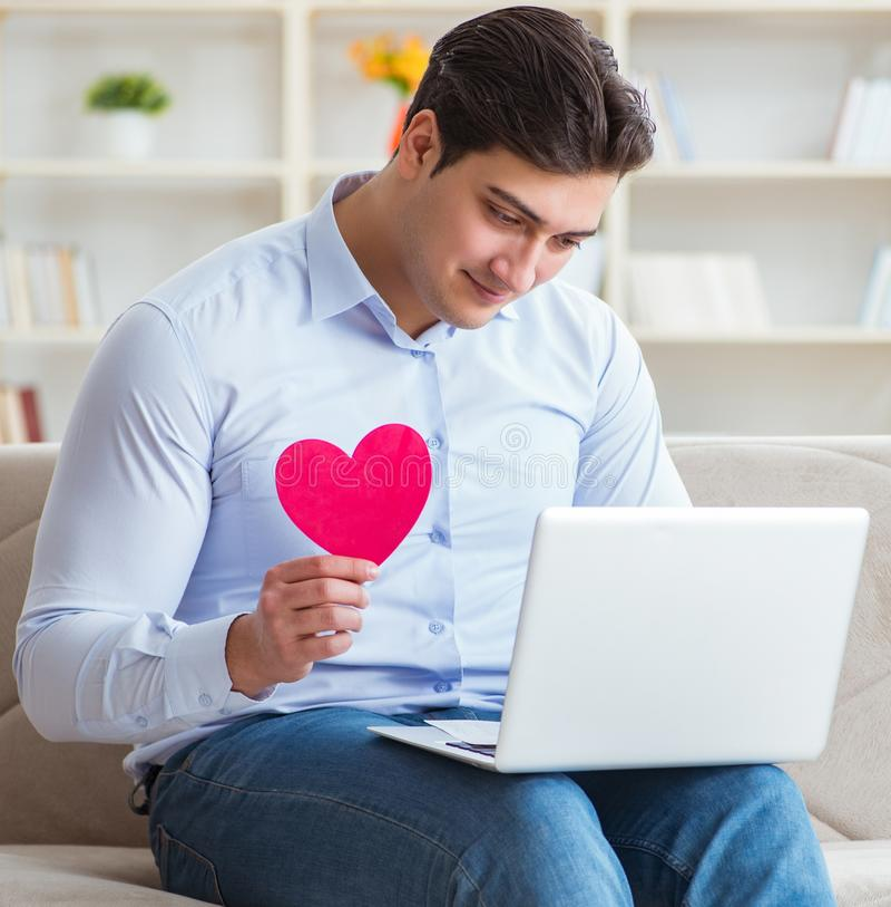 El hombre joven que hace propuesta de matrimonio sobre el ordenador port?til de Internet imagenes de archivo