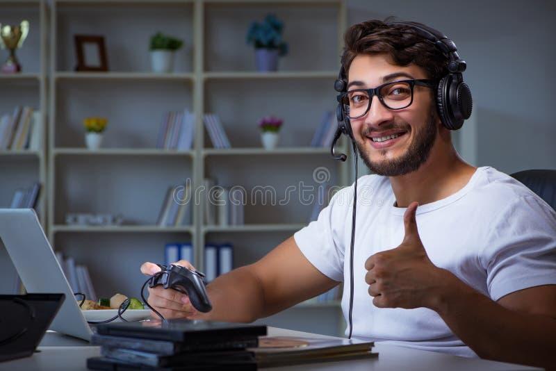 El hombre joven que juega las largases horas de los juegos atrasadas en la oficina foto de archivo libre de regalías