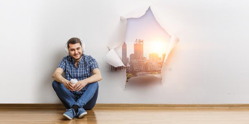 El hombre joven que se sienta en el piso, un momento para relaja concepto T?cnicas mixtas imagen de archivo libre de regalías