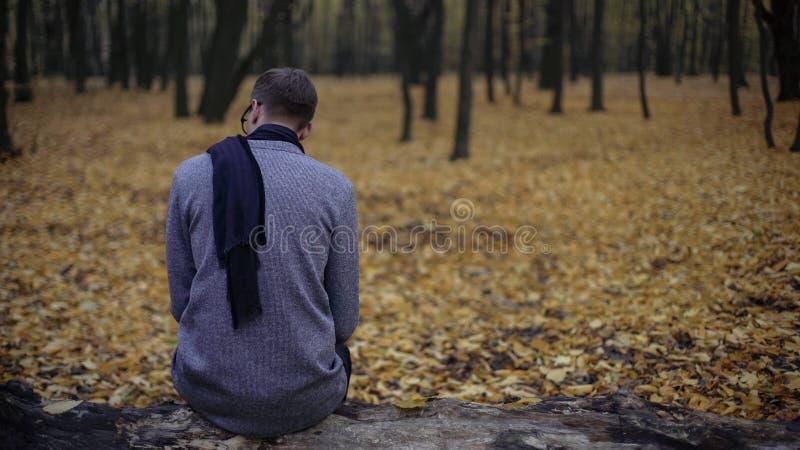 El hombre joven que se sienta solamente en parque del otoño, siente la depresión, nostalgia, soledad fotografía de archivo