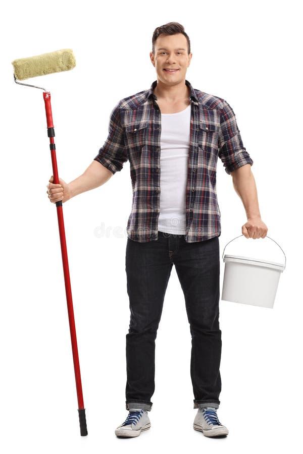 El hombre joven que sostiene un rodillo de pintura y un color bucket foto de archivo