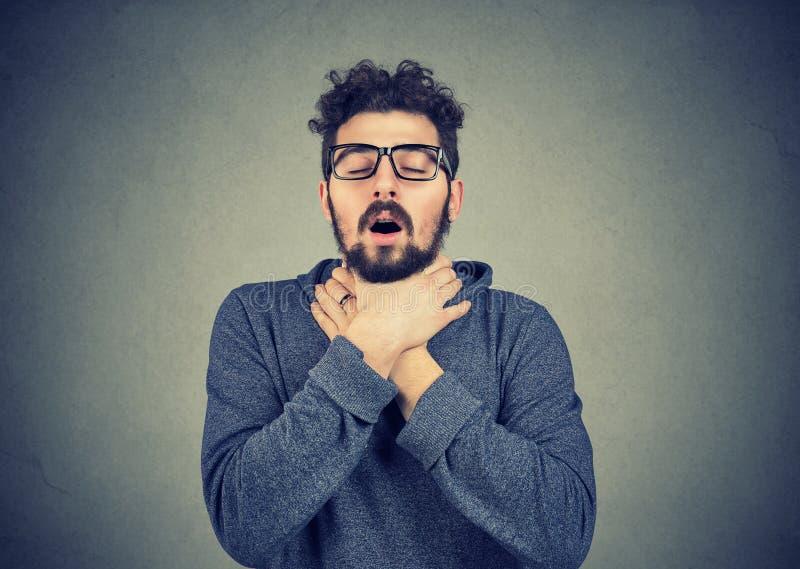 El hombre joven que tiene ataque de asma puede respiración del ` t fotografía de archivo