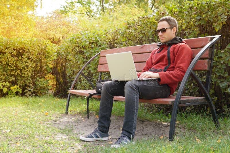 El hombre joven que trabaja en su ordenador port?til conecta con Internet inal?mbrico en zona rural La conexi?n a internet permit imagen de archivo libre de regalías