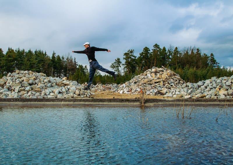 El hombre joven salta cerca de piedra y de bosque del waterwith fotos de archivo