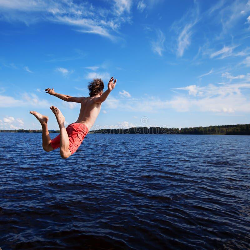 El hombre joven salta en agua imagen de archivo libre de regalías