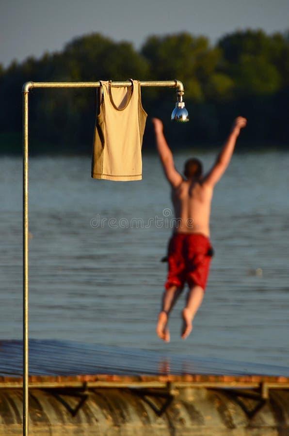 El hombre joven salta en el agua imagen de archivo