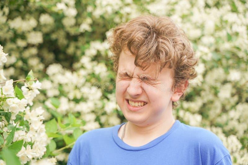 El hombre joven se coloca entre las flores y disfruta de verano y de florecimiento fotografía de archivo libre de regalías