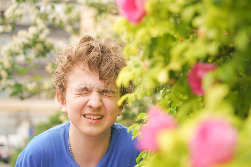 El hombre joven se coloca entre las flores y disfruta de verano y de florecimiento fotografía de archivo