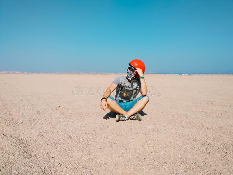 El hombre joven se sienta cuidadosamente en el medio del desierto que lleva un casco para el cochecillo imagenes de archivo