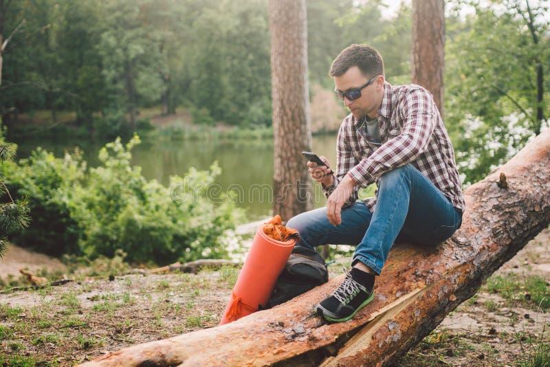 El hombre joven se sienta en el camión al bosque y usar el teléfono móvil el viajero del hombre se sienta en el árbol caido grand imagen de archivo libre de regalías