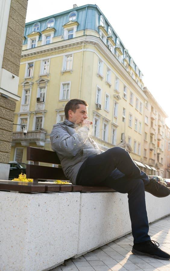 El hombre joven se sienta en un banco que fuma un cigarrillo electr?nico en la calle Vape fotos de archivo
