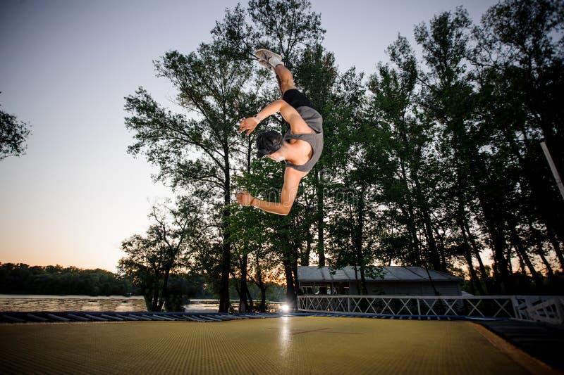 El hombre joven se vistió en la ropa informal trampolining en un parque imagen de archivo libre de regalías
