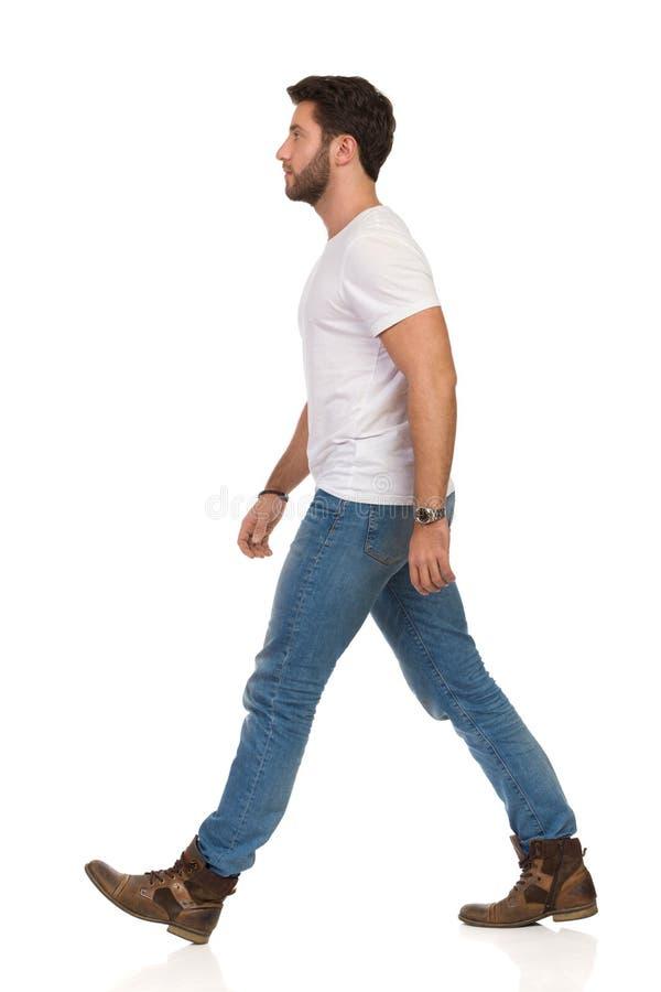 El hombre joven serio en vaqueros y la camiseta blanca est? caminando Vista lateral imagen de archivo libre de regalías