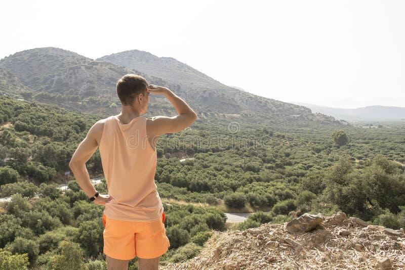 El hombre joven solo se coloca en la montaña y mira en la distancia concepto - la investigación, búsqueda, metas, se mueve adelan foto de archivo libre de regalías