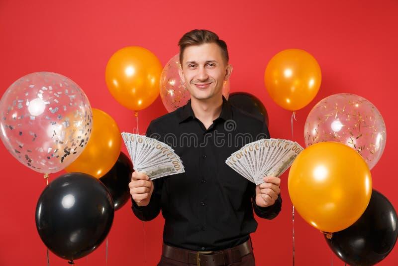El hombre joven sonriente en porciones clásicas negras del paquete de la tenencia de la camisa de dólares cobra el dinero en el b imagenes de archivo