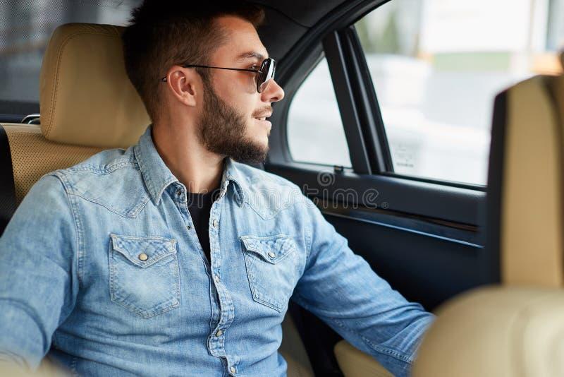 ] el hombre joven sonriente está mirando a través de la ventana del vehículo imagen de archivo