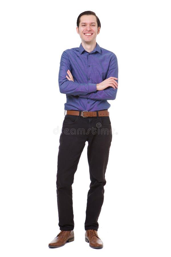 El hombre joven sonriente integral que se colocaba con los brazos cruzó en el fondo blanco imagen de archivo libre de regalías