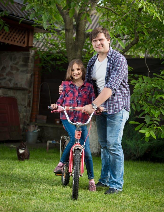 El hombre joven sonriente que enseña a su montar a caballo de la hija monta en bicicleta en el patio trasero de la casa imagenes de archivo