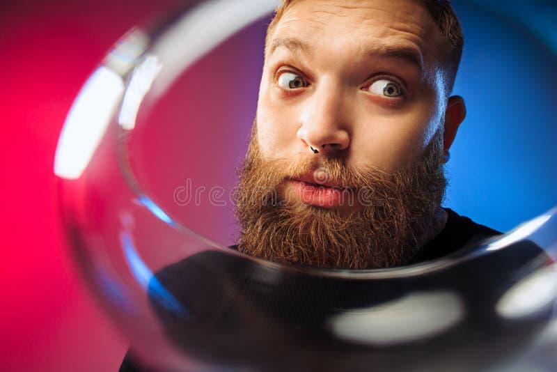 El hombre joven sorprendido que presenta con la copa de vino foto de archivo