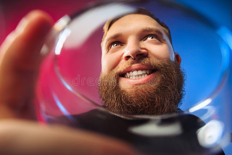 El hombre joven sorprendido que presenta con la copa de vino foto de archivo libre de regalías