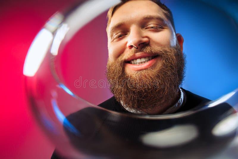 El hombre joven sorprendido que presenta con la copa de vino fotografía de archivo