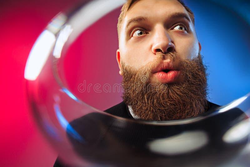 El hombre joven sorprendido que presenta con la copa de vino imagen de archivo